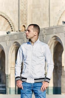 Porträt eines mannes auf dem hintergrund der hassan ii moschee in marokko, casablanca