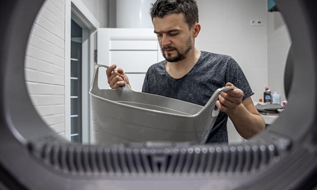 Porträt eines mannes, blick von der waschmaschine, laden und waschen von schmutziger wäsche.