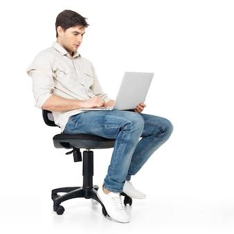 Porträt eines mannes, der am laptop arbeitet, der auf dem stuhl sitzt - lokalisiert auf weiß.