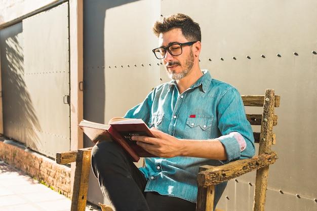 Porträt eines mannes, der auf dem stuhl liest das buch sitzt
