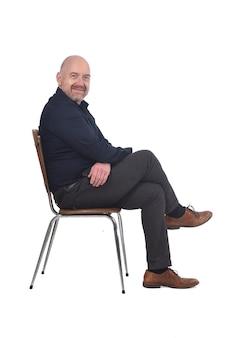 Porträt eines mannes, der auf einem stuhl im weißen hintergrund sitzt und kamera betrachtet