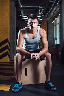 Porträt eines mannes, der auf holzkiste in der turnhalle sitzt