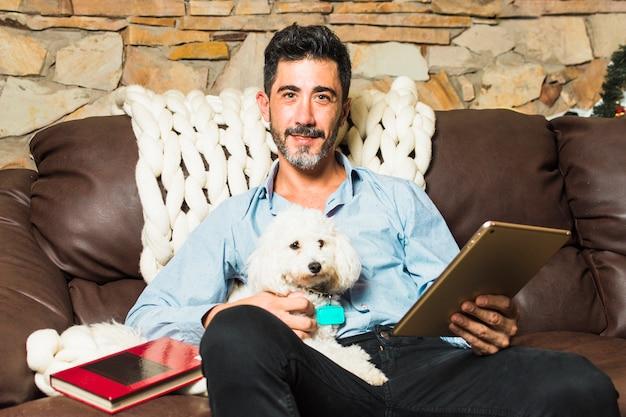 Porträt eines mannes, der auf sofa mit seinem weißen hund in der hand hält digitale tablette sitzt
