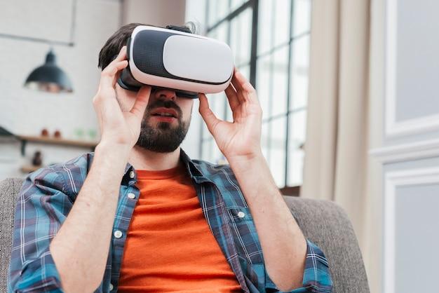 Porträt eines mannes, der auf tragenden gläsern der virtuellen realität des sofas sitzt