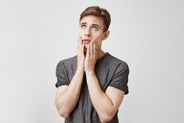 Porträt eines mannes, der aufschaut und seine hände auf gesicht schockiert hält.