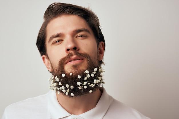 Porträt eines mannes, der blumen in einer bartmode-nahaufnahme aufwirft