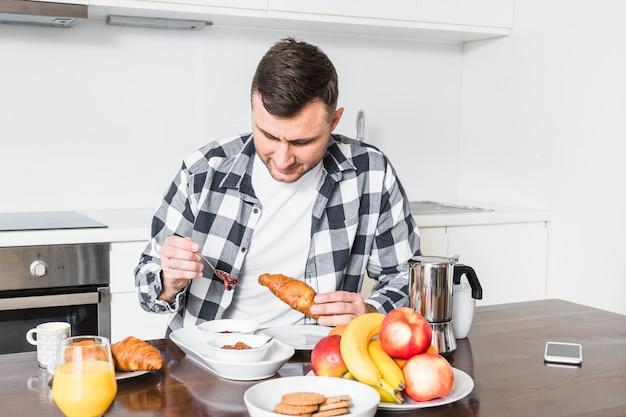 Porträt eines mannes, der das hörnchen in der küche genießt