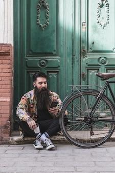 Porträt eines mannes, der den handy sitzt nahe dem fahrrad vor grüner holztür verwendet
