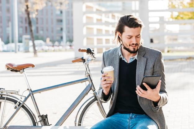 Porträt eines mannes, der die wegwerfkaffeetasse betrachtet das intelligente telefon sitzt nahe dem fahrrad hält