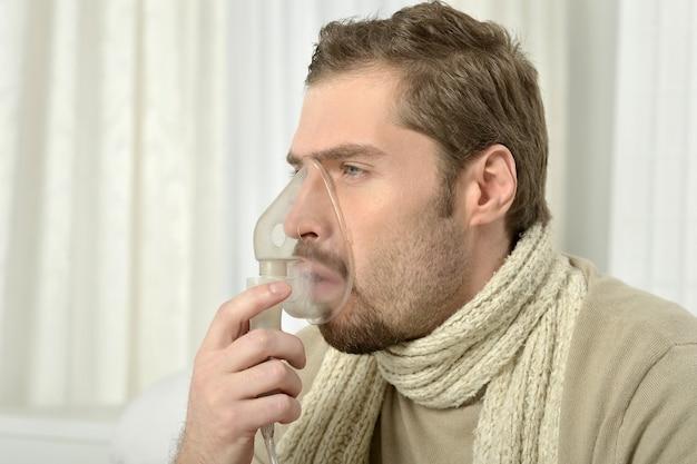 Porträt eines mannes, der durch inhalatormaske einatmet