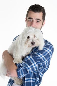 Porträt eines mannes, der ein maltesisches bischon des weißen hundes lokalisiert über weiß hält.