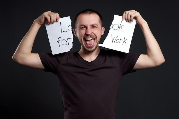 Porträt eines mannes, der eine inschrift auf papier zerreißt, die einen job sucht