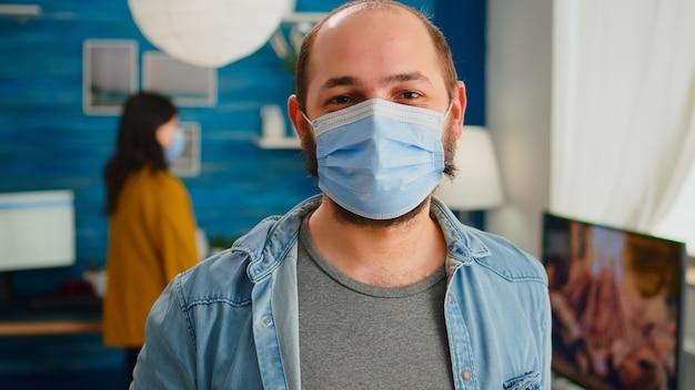 Porträt eines mannes, der eine schutzmaske aufsetzt und die kamera anschaut, die gute zeit mit freunden im wohnzimmer verbringt und die soziale distanz bei der globalen pandemie respektiert. menschen, die während des covid-19-ausbruchs kontakte knüpfen