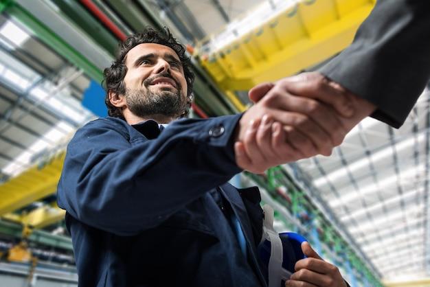 Porträt eines mannes, der einen händedruck in einer industriellen anlage gibt