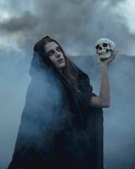 Porträt eines mannes, der einen schädel in der dunkelheit hält und kamera betrachtet