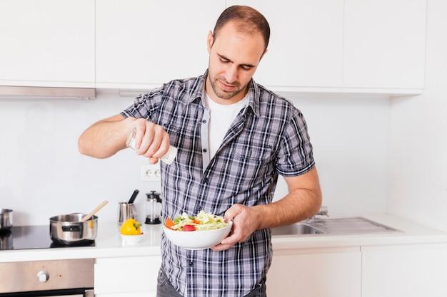 Porträt eines mannes, der gewürze in der salatschüssel hinzufügt