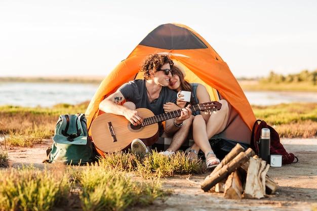 Porträt eines mannes, der gitarre für seine freundin spielt, die am strand kampiert