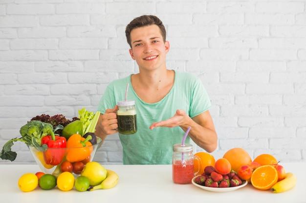Porträt eines mannes, der grünes smoothieflasche mit vielen gesundem lebensmittel auf tabelle hält