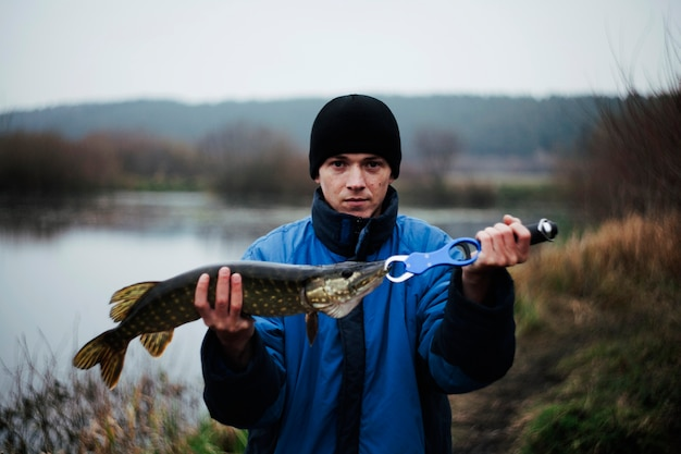 Porträt eines mannes, der hechtfisch hält