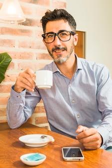 Porträt eines mannes, der in der hand kaffeetasse mit handy auf tabelle hält