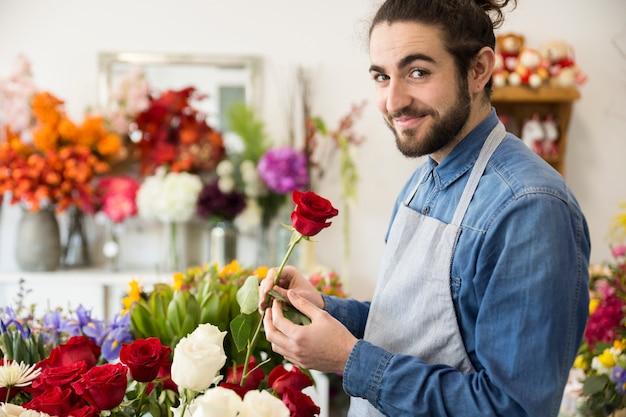 Porträt eines mannes, der in der hand rote rosenblume schaut zur kamera hält