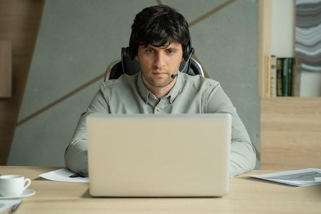 Porträt eines mannes, der in die kamera schaut und einen videoanruf aus dem büro hat