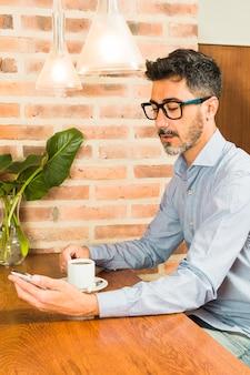 Porträt eines mannes, der in trinkendem kaffee des cafés betrachtet handy sitzt