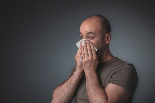 Porträt eines mannes, der seine nase mit einem gewebe durchbrennt