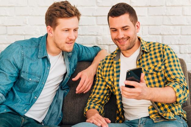 Porträt eines mannes, der seinem freund auf smartphone etwas zeigt