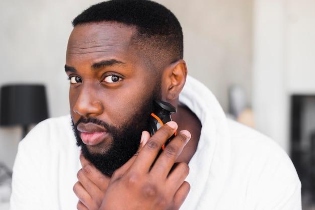 Porträt eines mannes, der seinen bart rasiert