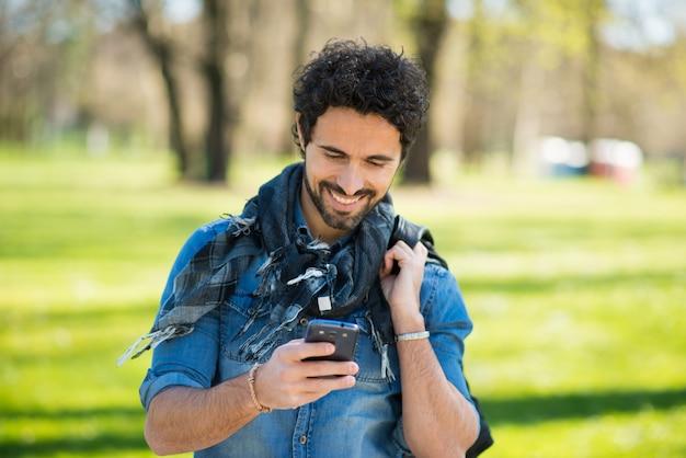 Porträt eines mannes, der seinen handy in einem park verwendet