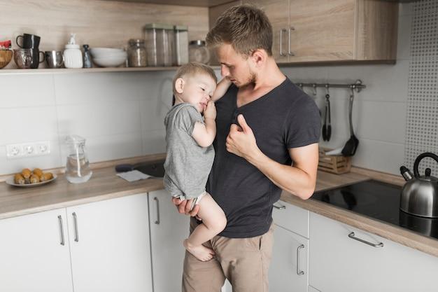 Porträt eines mannes, der seinen kleinen sohn steht im küchengestikulieren trägt
