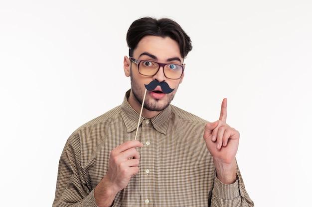 Porträt eines mannes, der stock mit schnurrbart hält und mit dem finger nach oben zeigt, isoliert auf einer weißen wand