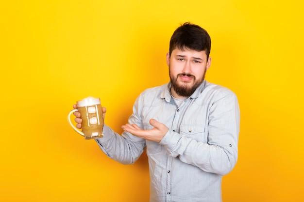 Porträt eines mannes, der über die qualität des bieres empört ist, foto auf einer gelben wand