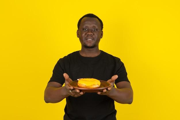 Porträt eines mannes im schwarzen t-shirt, der gelb glasierten donut gegen gelbe wand hält