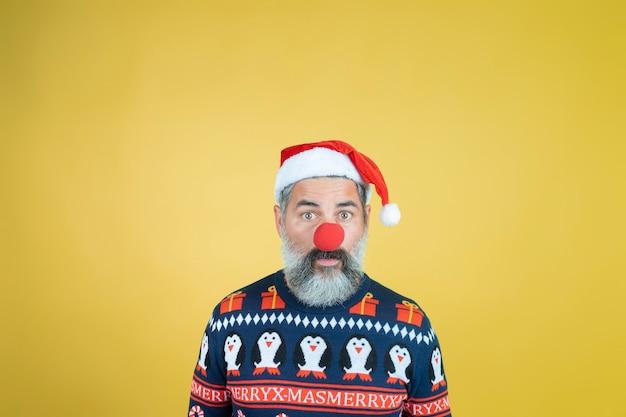 Porträt eines mannes im weihnachtsmannhut mit roter clownnase auf gelb