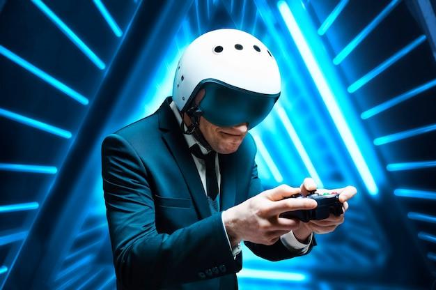 Porträt eines mannes in anzug und helm eines piloten mit einem joystick in den händen. begeistert spielt er ein computerspiel. spielraum. spielkonzept. gemischte medien
