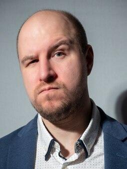 Porträt eines mannes in den dreißigern, der ein hemd und eine jacke auf grauem hintergrund trägt. er spitzte die lippen und hob eine augenbraue. kleines haar auf dem kopf, ein bart. hochmütiger blick. vertikales foto