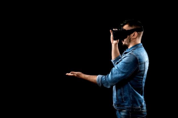 Porträt eines mannes in den gläsern der virtuellen realität, vr, gegen einen dunklen hintergrund.