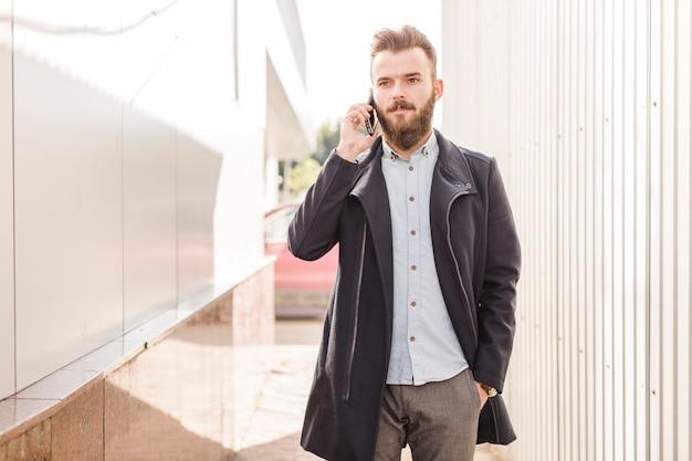 Porträt eines mannes in der schwarzen jacke sprechend auf mobiltelefon