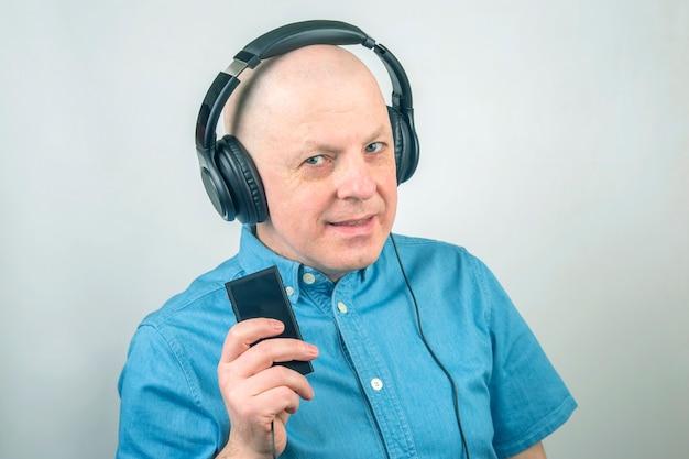 Porträt eines mannes in einem blauen hemd mit kopfhörern in der entspannung, die musik hört