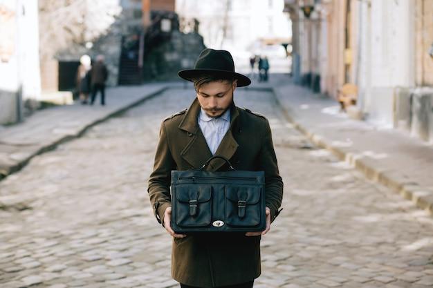 Porträt eines mannes in einem mantel auf einer stadtstraße