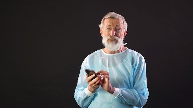 Porträt eines mannes in einem medizinischen anzug mit einem smartphone in seinen händen auf einem isolierten dunklen raum.
