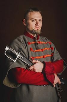 Porträt eines mannes in einem mittelalterlichen kostüm auf einem dunklen hintergrund. kleidung des polnischen adels.