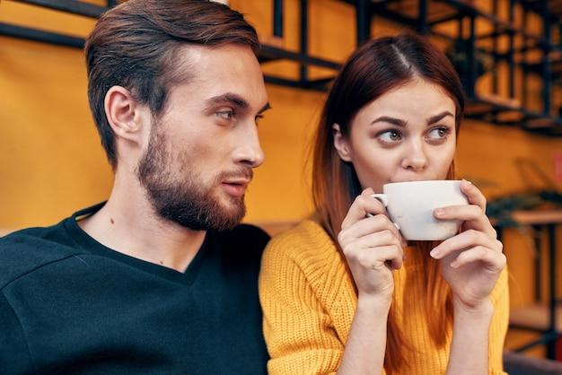 Porträt eines mannes in einem pullover und einer frau mit einer tasse kaffee innenraum