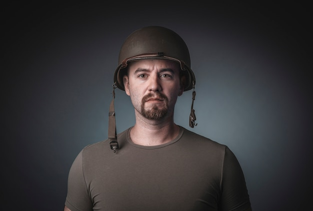 Porträt eines mannes in einem t-shirt, das einen soldatmilitärsturzhelm trägt,