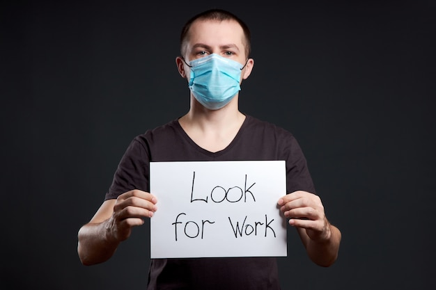 Porträt eines mannes in einer medizinischen maske mit einem zeichen, das nach arbeit an einer dunklen wand, coronavirus-infektion sucht
