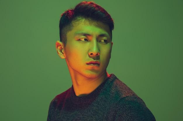 Porträt eines mannes mit buntem neonlicht auf grünem studiohintergrund. männliches model mit ruhiger und ernster stimmung. gesichtsausdruck, cyberpunk, millennials lifestyle und aussehen. zukunft, technologien.