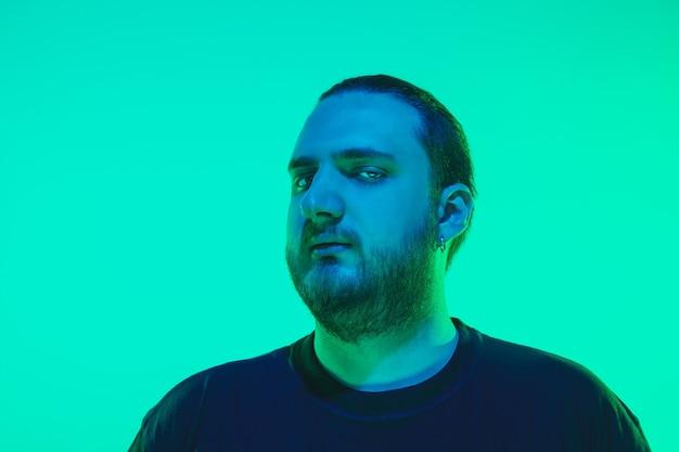 Porträt eines mannes mit buntem neonlicht auf grüner wand. männliches model mit ruhiger und ernster stimmung. gesichtsausdruck, millennials lifestyle und aussehen. zukunft, technologien.