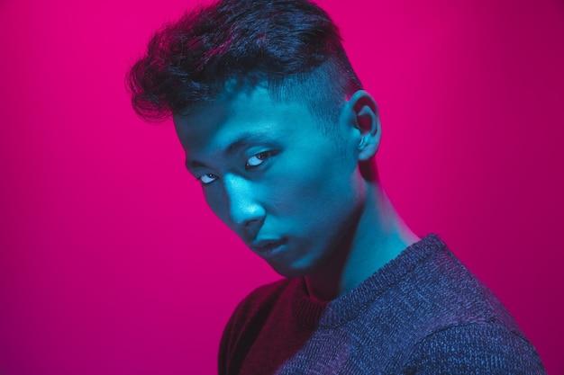 Porträt eines mannes mit buntem neonlicht auf rosa studiohintergrund. männliches model mit ruhiger und ernster stimmung. gesichtsausdruck, cyberpunk, millennials lifestyle und aussehen. zukunft, technologien.